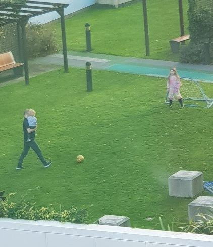 family playing in manchester house garden